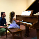 girl playing piano while teacher watches