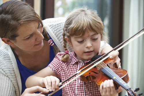 girl playing violin while teacher helps