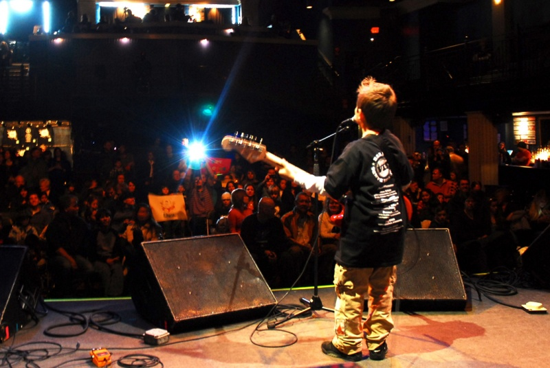 kid playing guitar on stage