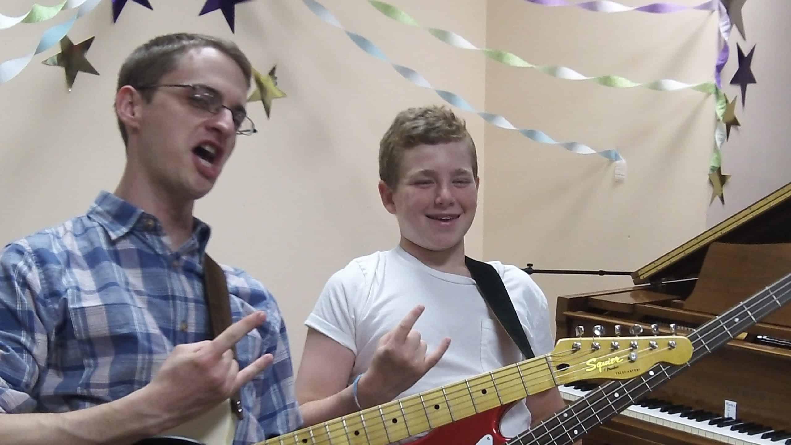 guitar teacher and student give happy devil horns at a recital