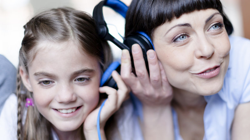 mom and daughter listening to same headphones