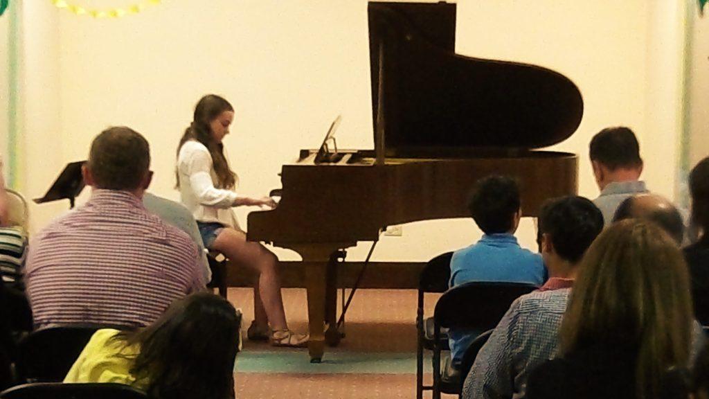 girl playing piano at a recital