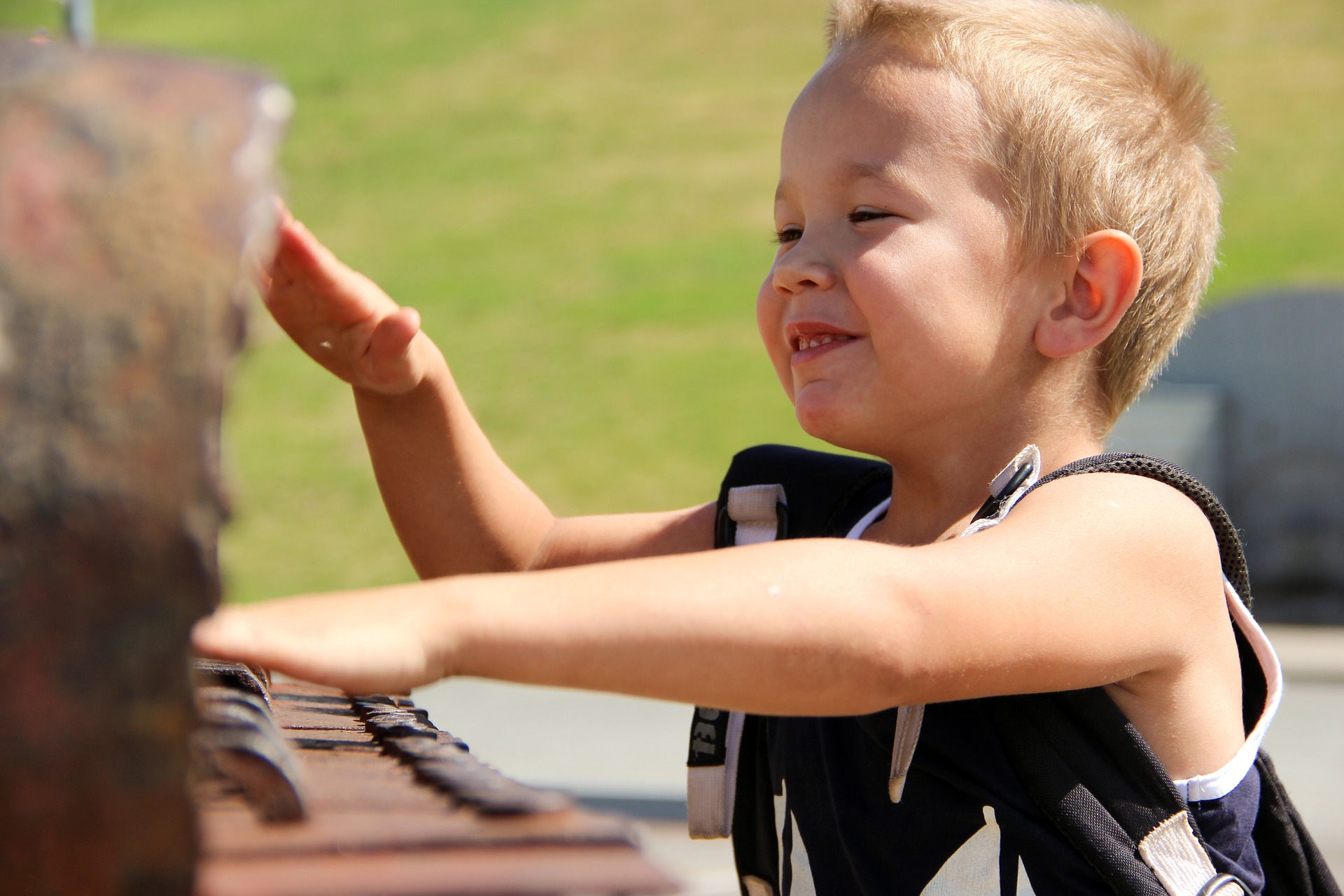 Little happy boy playing piano outside
