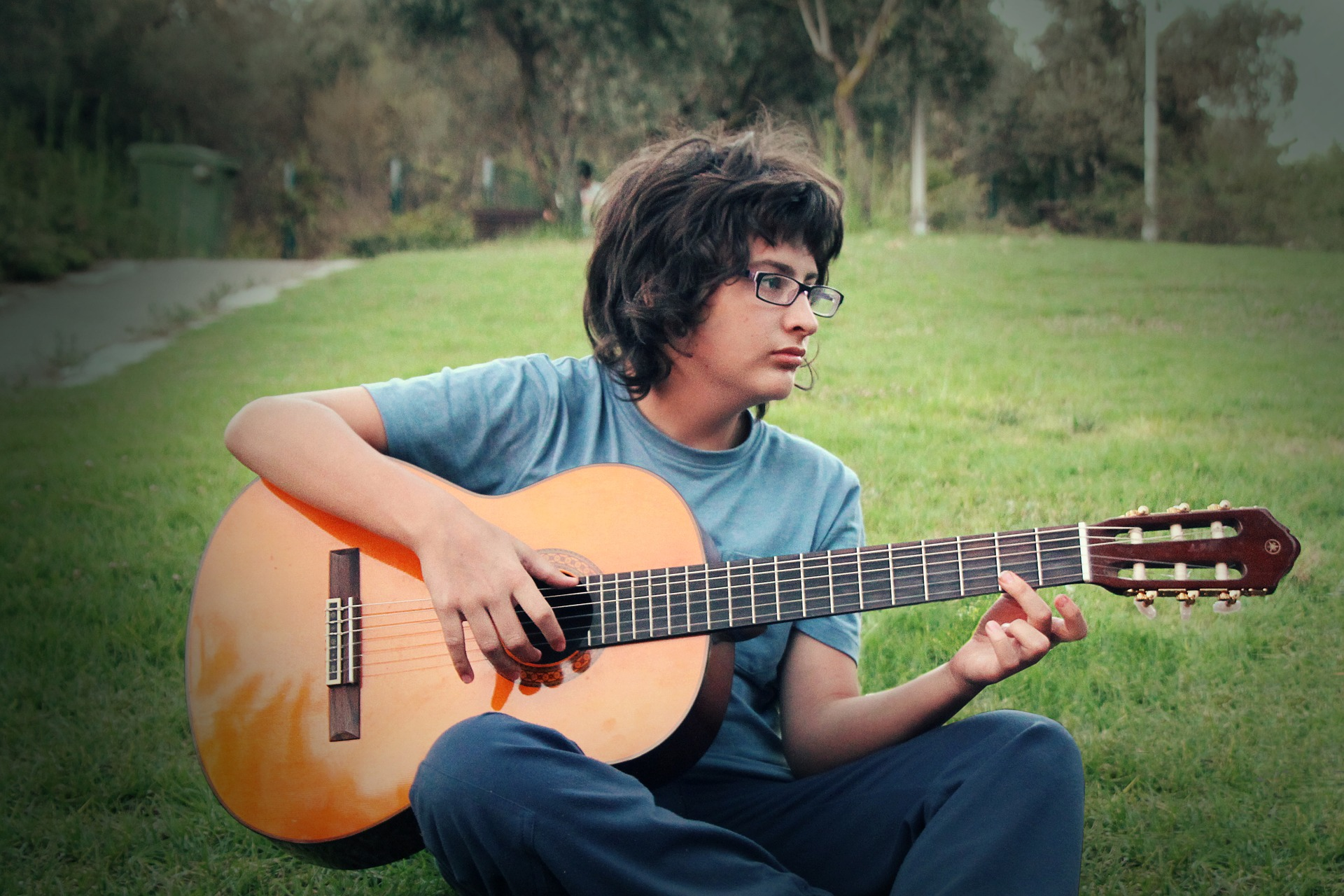 teen boy playing guitar in grass