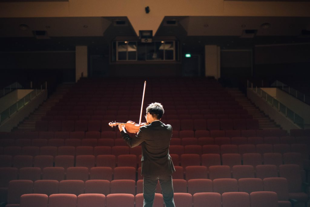 boy playing violin to an empty theater