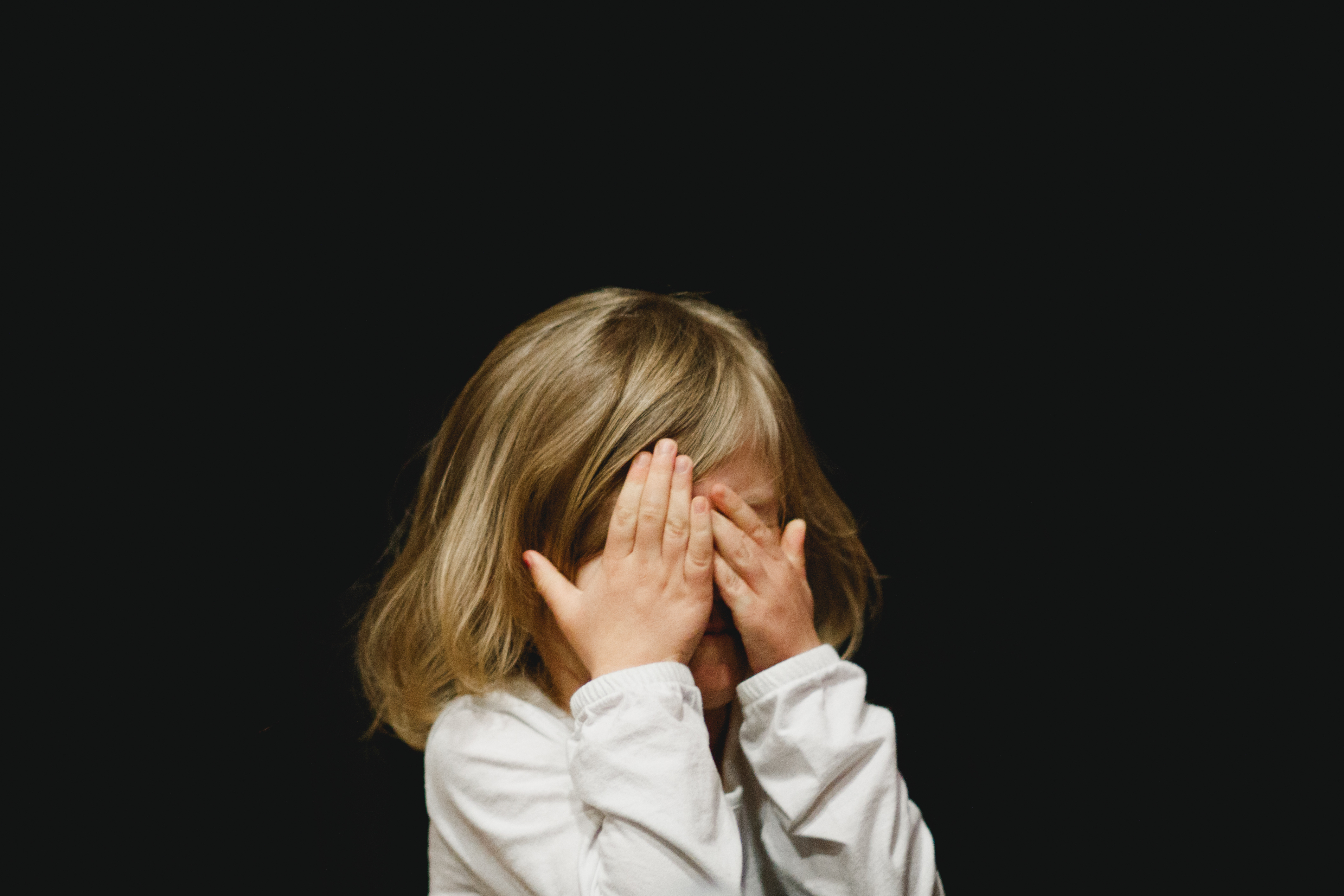 shy little girl covering her face with her hands