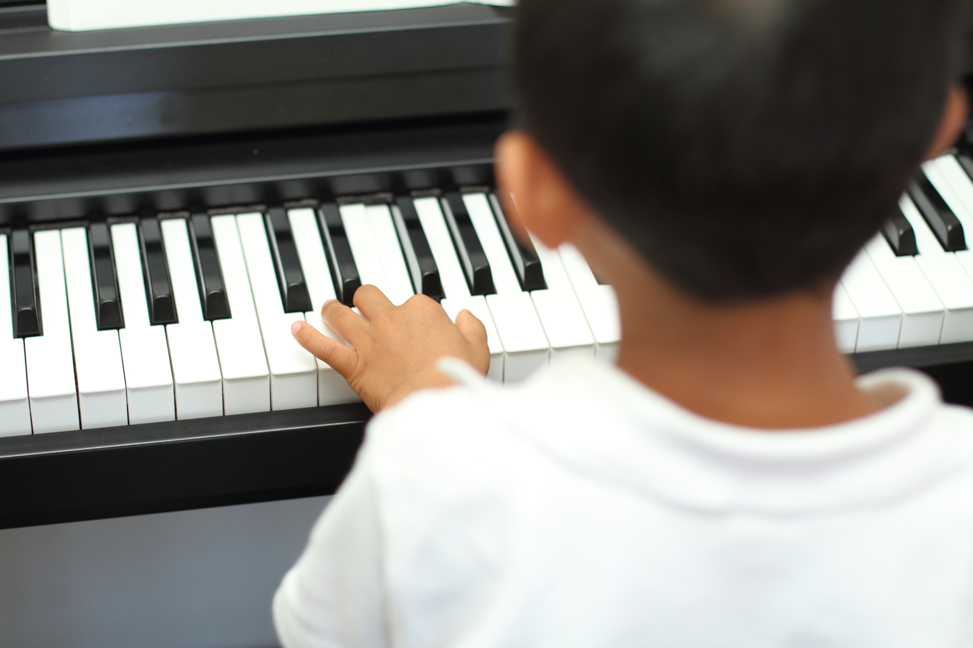 Japanese boy playing digital pianos