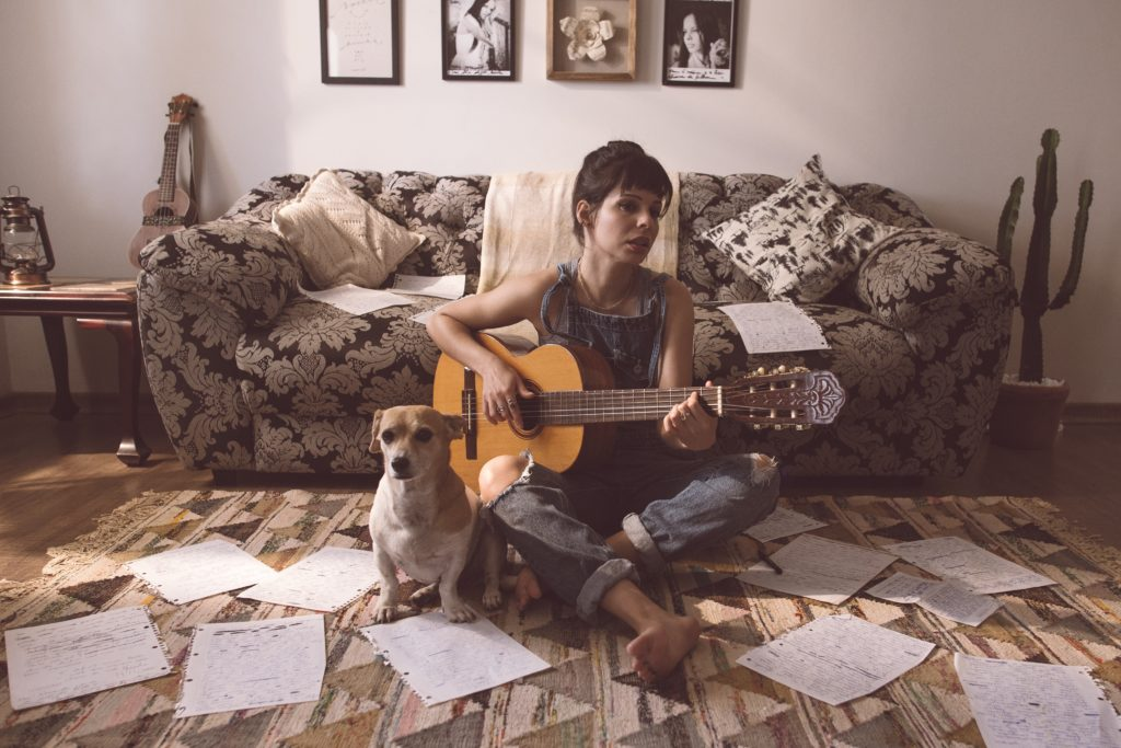 woman playing guitar on floor