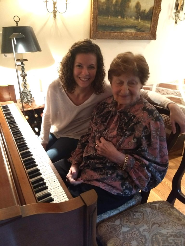 Young piano teacher and older piano student with Alzheimer's at piano