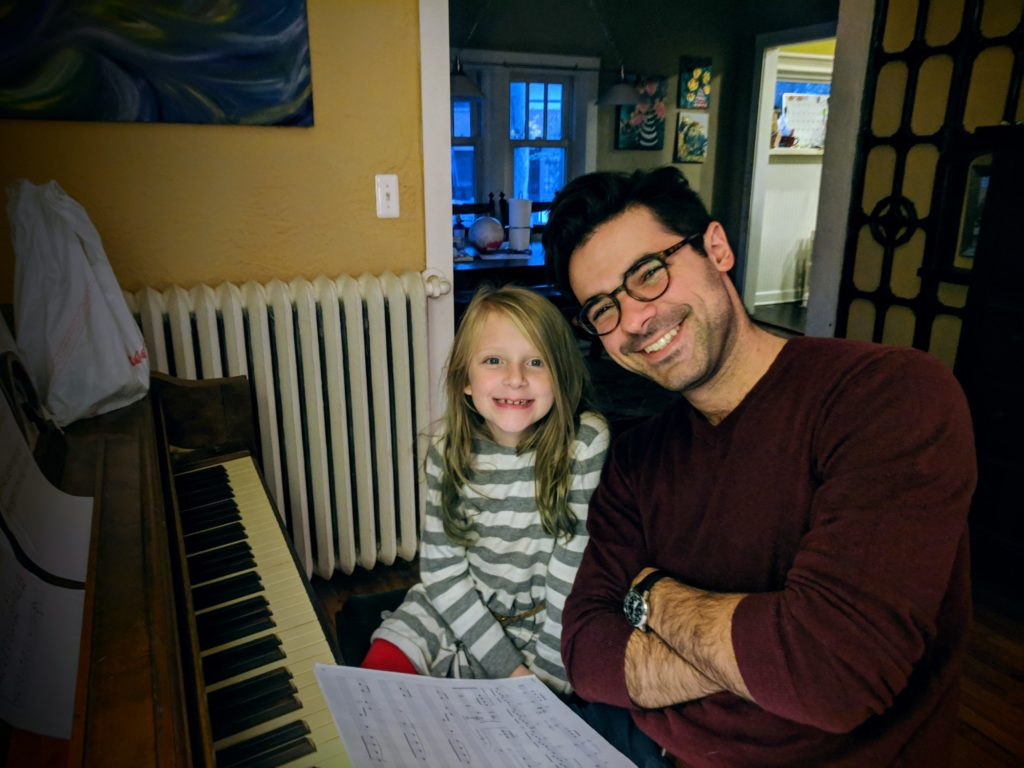 Little girl smiles at the piano with her Deerfield piano teacher