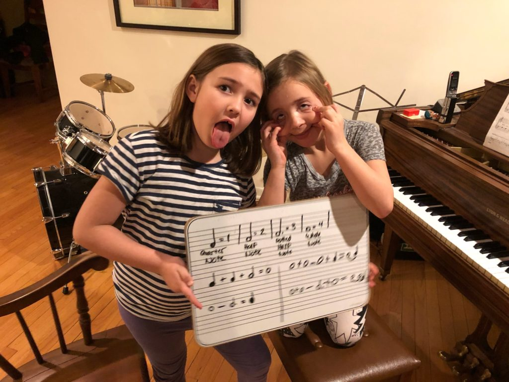 two little girls making faces at piano