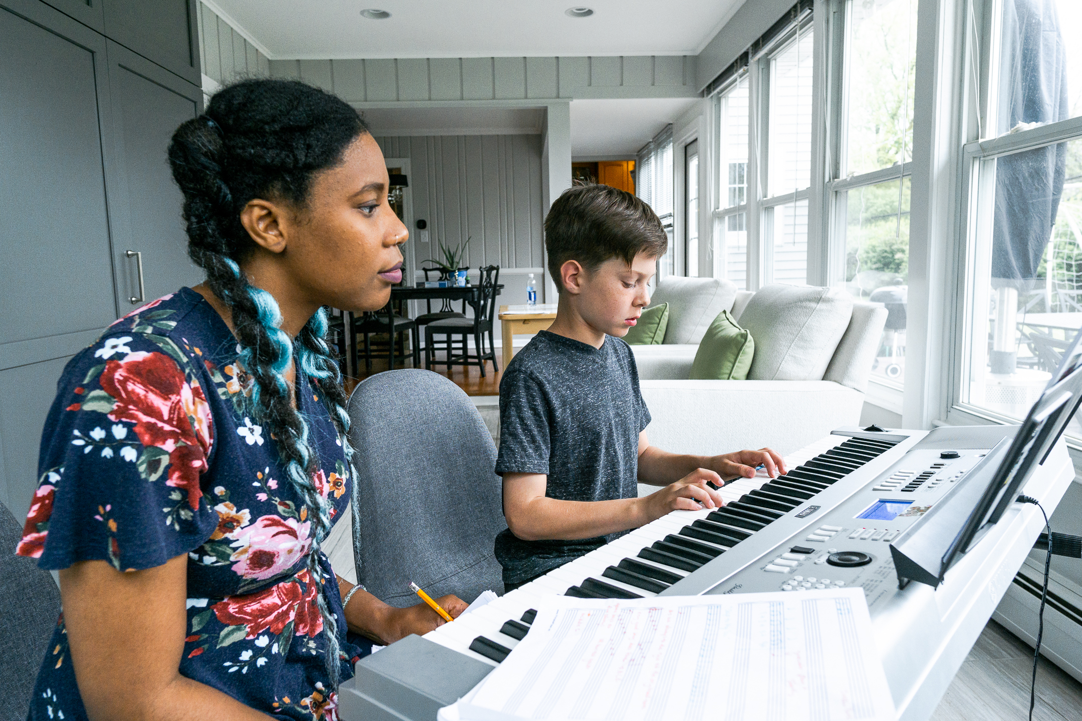 woman teaching younger student piano