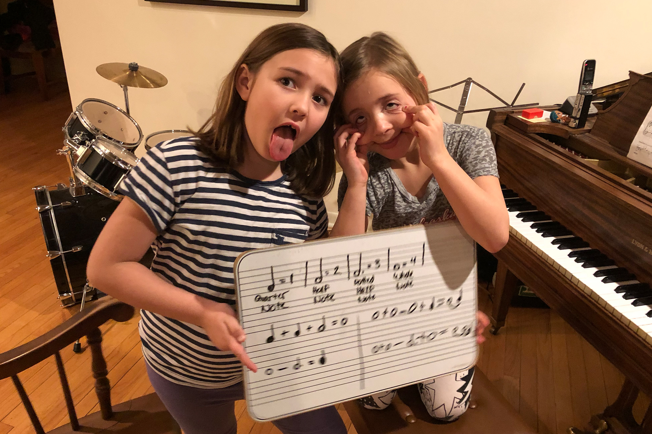 girls making funny faces holding up sheet music in front of piano